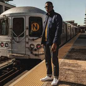 our fit model wearing The Taylor Stitch x Alpha Industries M-51 in Indigo Reverse Sateen—standing near subway tracks