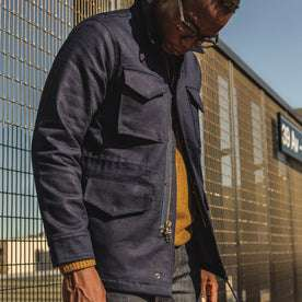our fit model wearing The Taylor Stitch x Alpha Industries M-51 in Indigo Reverse Sateen—looking down
