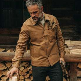 our fit model wearing The Reversible Lombardi Jacket in Arid Camo—holding axe