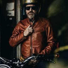 our fit model wearing The Band Collar Moto Jacket—helmet on, in the garage