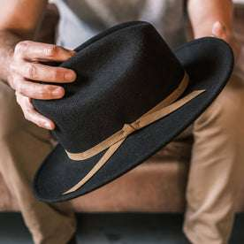 fit model wearing The Packable Lane Splitter in Espresso, holding hat