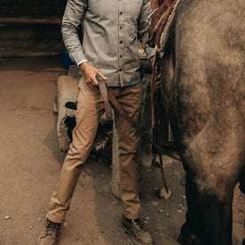 fit model wearing The Slim All Day Pant in Rustic Oak Organic Selvage, next to horse