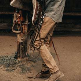 fit model wearing The Slim All Day Pant in Rustic Oak Organic Selvage, next to saddle