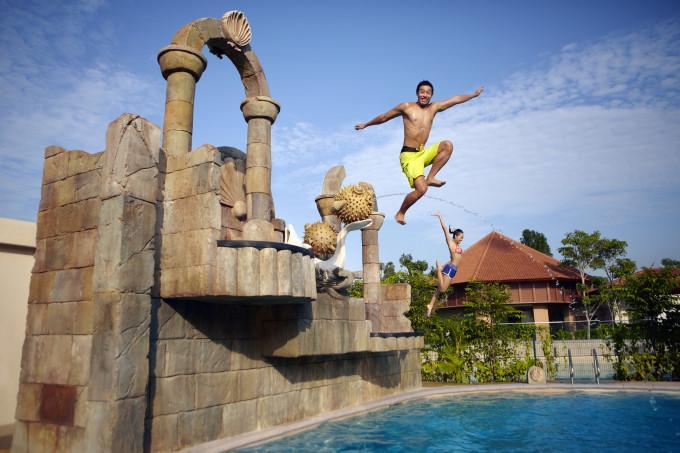 guy jumping into the swimming pool at adventure cove waterpark