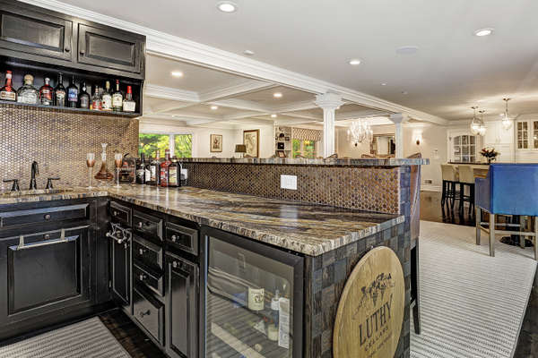 WET BAR BOASTS A BEVERAGE COOLER AND BAR SEATING