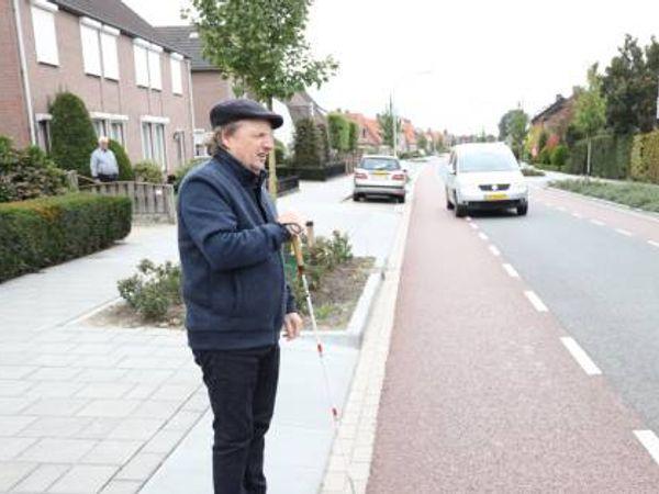 Blinde man staat bij fietspad klaar om over te steken