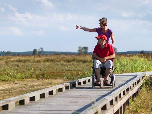 Man in rolstoel op het rolstoel wandelpad