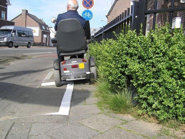 Persoon in elektrische rolstoel op een te smalle stoep