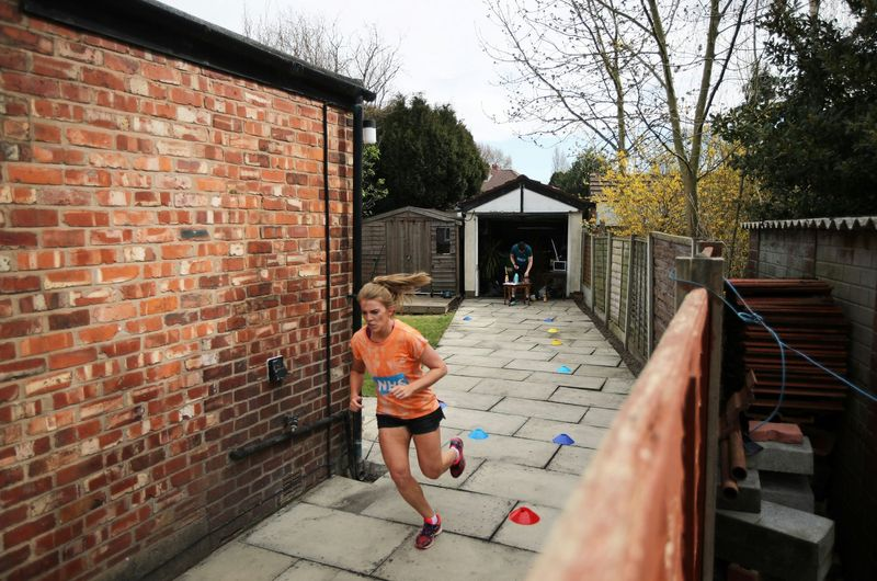 Social distancing photos - woman running a marathon in her yard