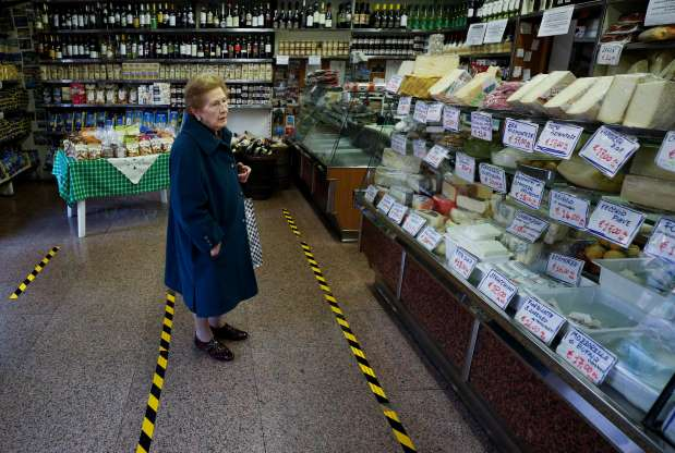Social distancing photo gallery - old woman shopping for food in Italy