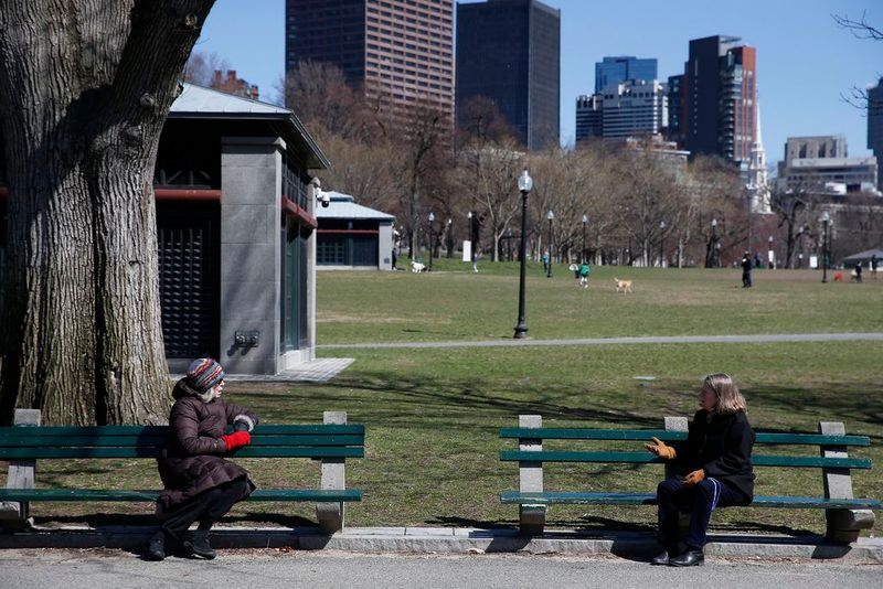 Social distancing photos - two women talking sitting in separate benches at the park