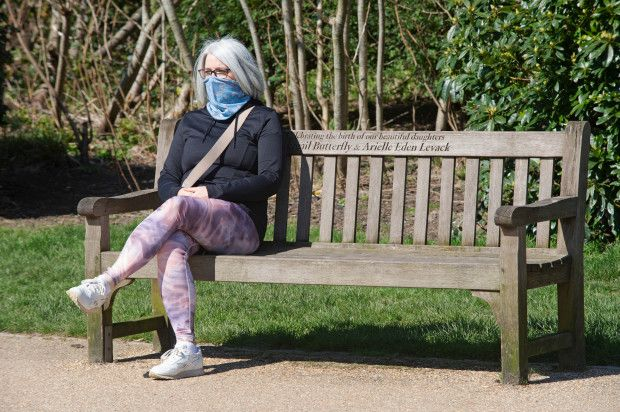 Social distancing photos - woman sitting on bench in the park wearing a mask