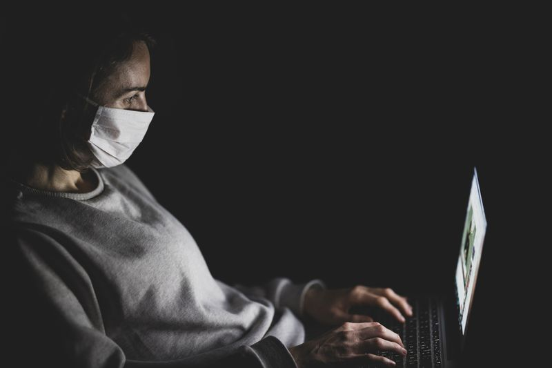 Coronavirus fake news - man wearing a face mask in front of her laptop in the dark