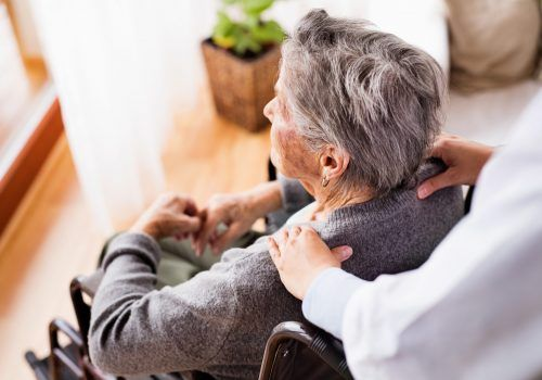 Health visitor and a senior woman during home visit. Unrecognizable nurse giving woman shoulder massage.