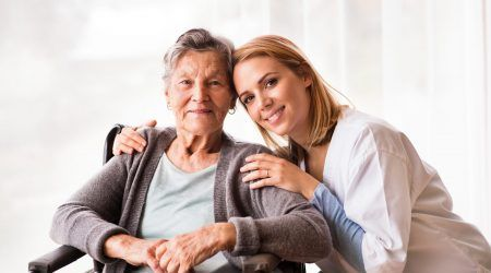 Health visitor and a senior woman during home visit. Portrait of a nurse and an elderly woman in an wheelchair.
