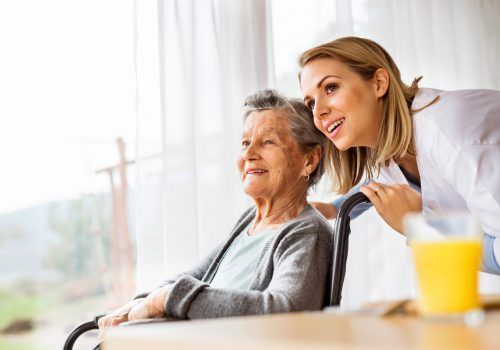 Health visitor and a senior woman during home visit. A nurse talking to an elderly woman in an wheelchair.