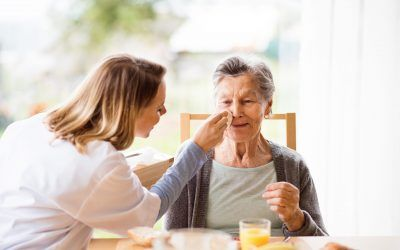 Health visitor and a senior woman during home visit. A nurse and an elderly woman sitting at the table.