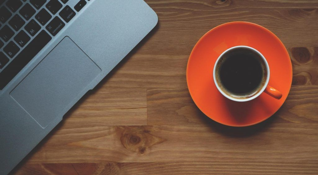 Laptop beside cup of black coffee