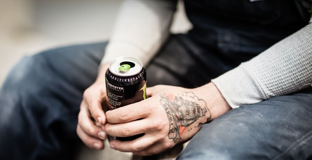 Tattooed man holding monster energy drink