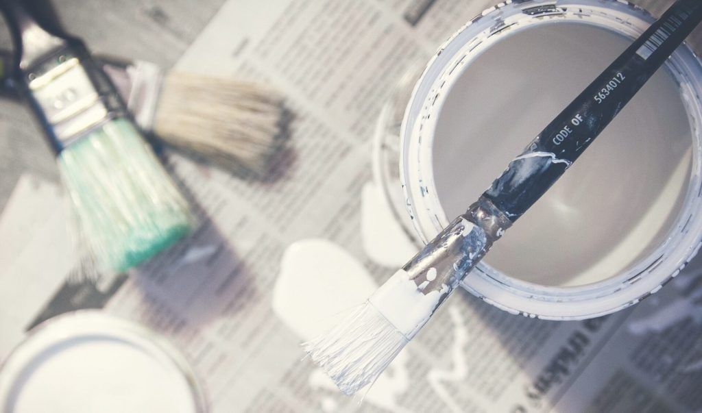 Tin of white paint with brush