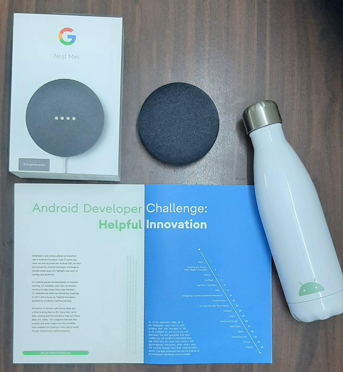 A bottle, Google Nest Mini and the magazine