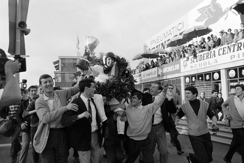 Race winner Jackie Stewart is carried through the pit lane after the podium celebration.