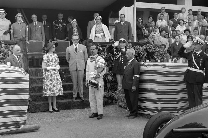 Maurice Trintignant receives his trophy from Prince Rainier and Princess Grace at the 1958 Monaco Grand Prix.