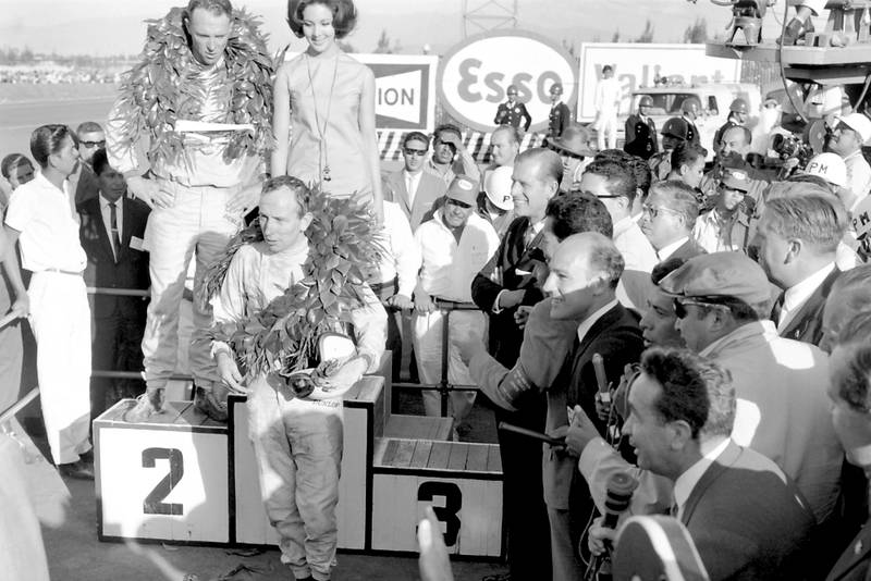 Race winner Dan Gurney stands on the podium with 2nd placed John Surtees standing below. Stirling Moss stands to the right with the media.