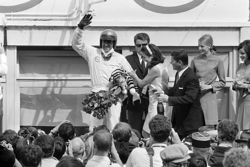 Jack Brabham, 1st position, celebrates on the podium.