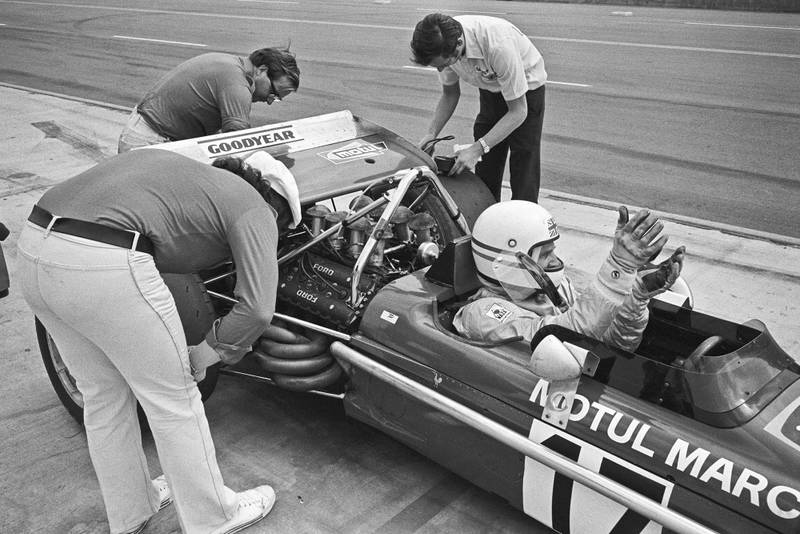 ONTARIO, CA - MARCH 28: Derek Bell waits for mechanics working on his March 701 at the Questor Grand Prix in which Formula One cars competed with Formula A cars on March 28, 1971 in Ontario, California.