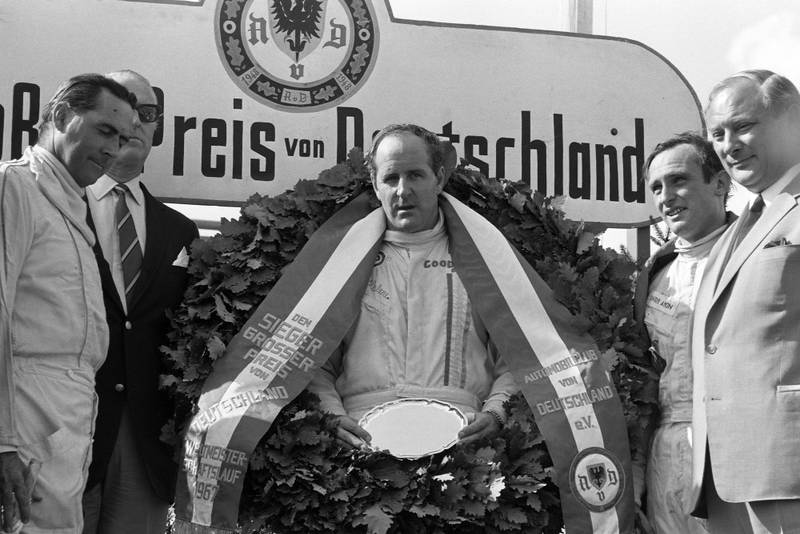 Race winner Denny Hulme on the podium with Jack Brabham, 2nd position, and Chris Amon, 3rd position.