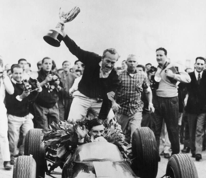 Colin Chapman sits on the back of Jim Clark's Lotus as the pair celebrate winning the 1963 F1 world championship at the Italian Grand Prix