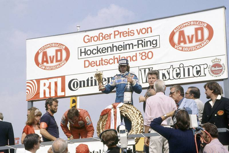 Jacques Laffite (Ligier JS11/15-Ford Cosworth), 1st position. Also visable on the podium are Carlos Reutemann (Williams FW07B-Ford Cosworth), 2nd position and FISA President Jean-Marie Balestre.