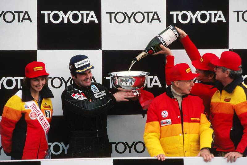 Race winner Alan Jones (Williams) celebrates his victory with champagne on the podium