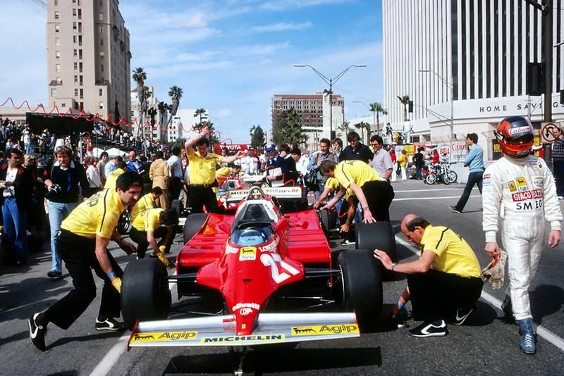 Gilles Villeneuve walks away from his Ferrari 126CK that is being serviced by his mechanics.