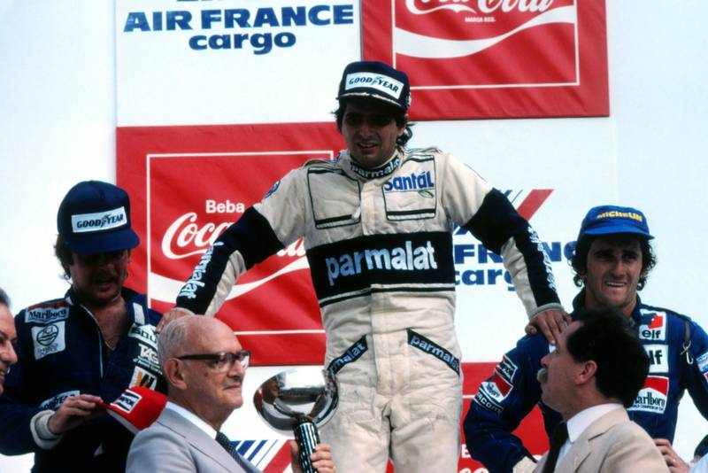On the podium, 1st Nelson Pique (centre), 2nd Keke Rosberg (lef), 3rd Alain Prost (right). An exhausted Piquet supports himself on the shoulders of Rosberg and Prost before collapsing.