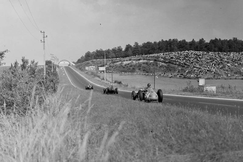Jean Behra in a BRM P25, leads Stirling Moss in his Vanwall, and Juan Manuel Fangio's Maserati 250F.