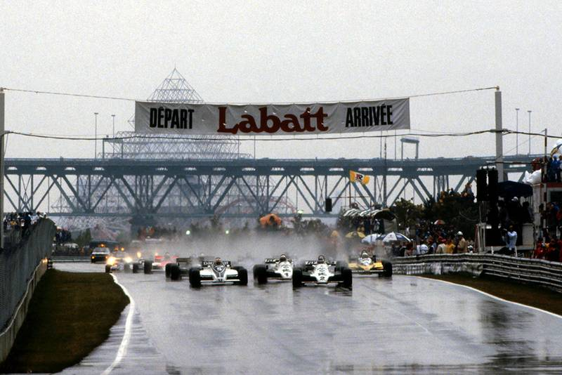 Carlos Reutemann in a Williams FW07C, leads from the line after starting from second on the grid.