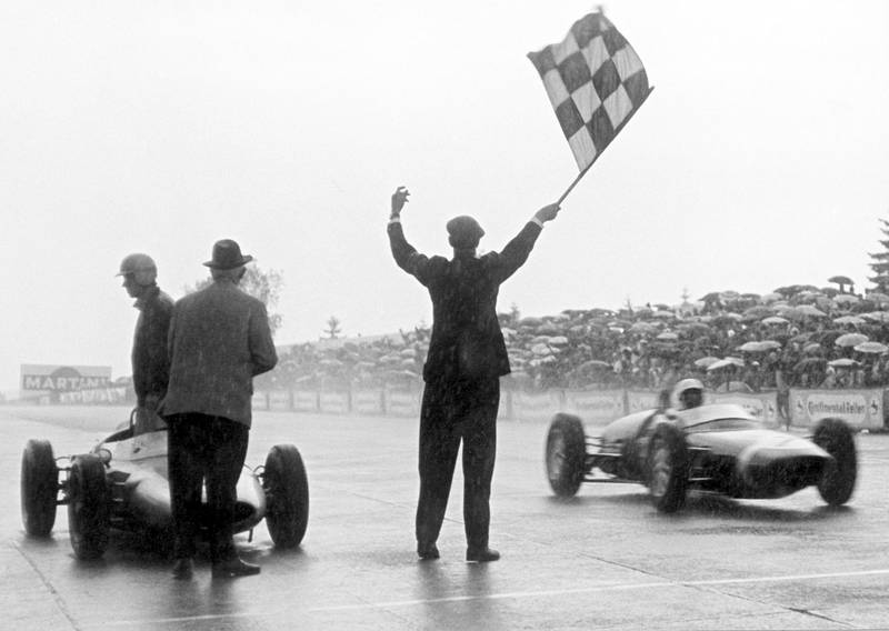Stirling Moss takes the flag in his Lotus 18/21-Climax.