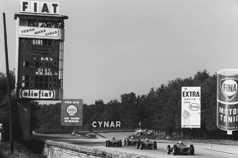 Four Ferrari Dino's 156 race down the main straight.