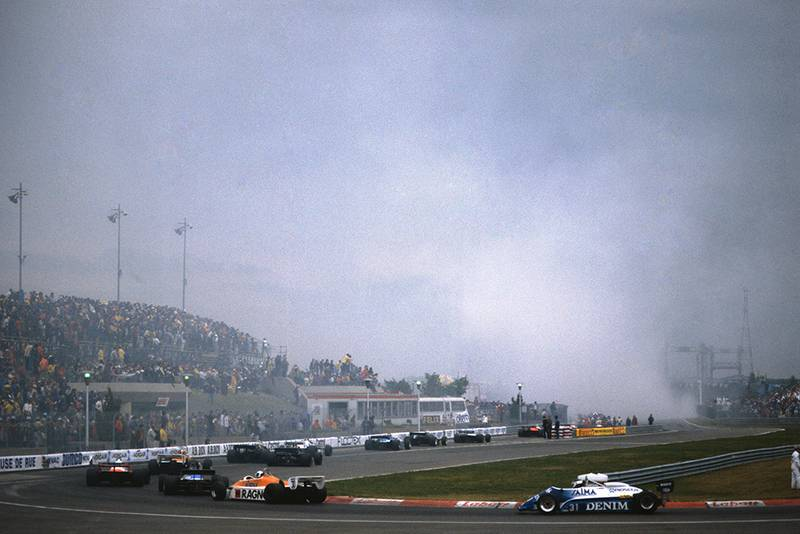Cars return to the pits as smoke rises from the startline accident in which Riccardo Paletti lost his life.