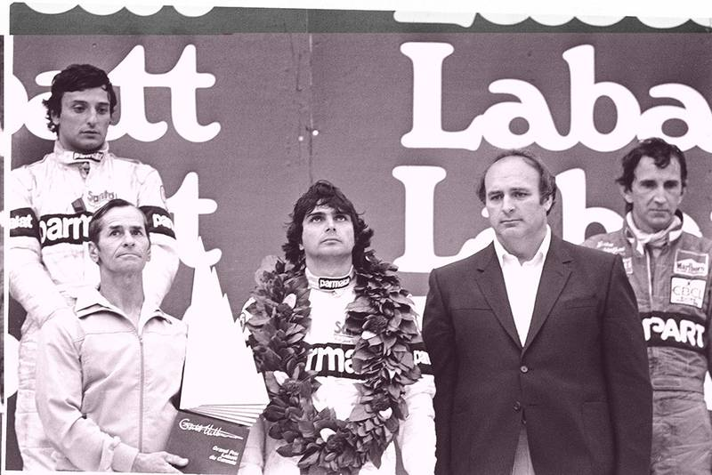 Nelson Piquet, 1st position, Riccardo Patrese, 2nd position and John Watson, 3rd position on the podium with Gilles Villeneuve father, Seville, holding the winners trophy.