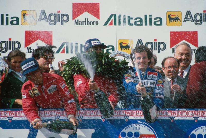 Race winner Patrick Tambay, centre, with second place Alain Prost, right, and third place Rene Arnoux, spray the champagne.