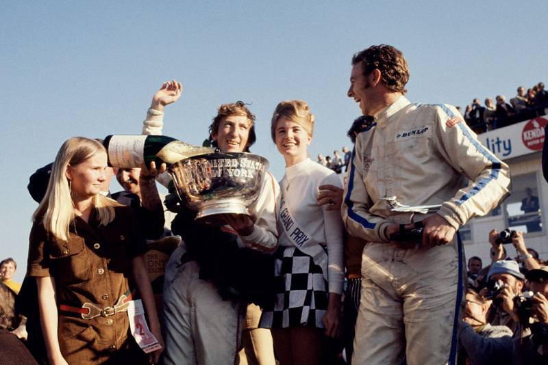 Jochen Rindt celebrates on the podium after winning the 1969 United States Grand Prix