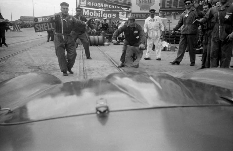 The Ferrari driven by Peter Collins and Louis Klemantaski arrives in the pit lane for refuelling during the Mille Miglia, April 1956. Louis Klemantaski: 'Coming in at high speed for our second refuelling, my heart stopped when the waiting mechanics were about to be annihilated. But such was their faith that they stood their ground and we halted just as the bonnet touched Parenti?s flag.' (Photo by Klemantaski Collection/Getty Images)