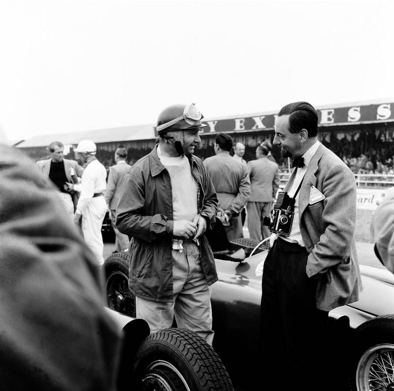 The British Grand Prix; Silverstone, July 14, 1956. Before the start of the race Juan Manuel Fangio, the best driver, chats with his friend Louis Klemantaski, the best motor racing photographer. Fangio went on to win. (Photo by Klemantaski Collection/Getty Images)