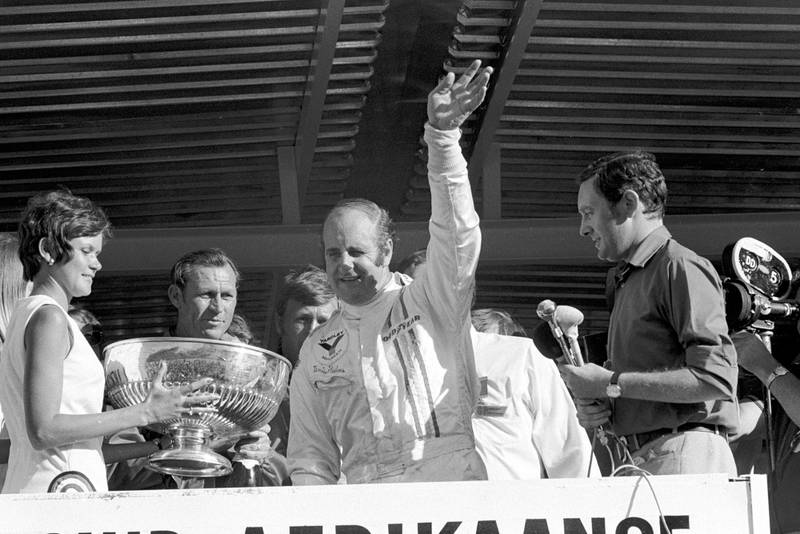 Denny Hulme waves from the podium after winning the 1972 South African Grand Prix.
