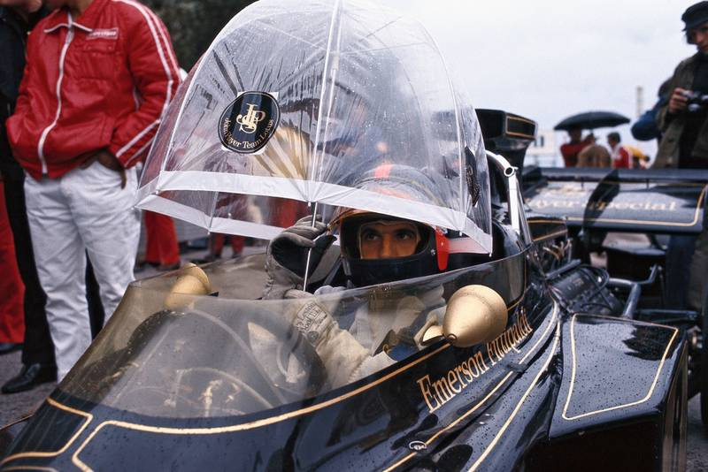Emerson Fittipaldi uses an umbrella for cover whilst sitting in his car waiting for the 1972 Monaco Grand Prix to start.
