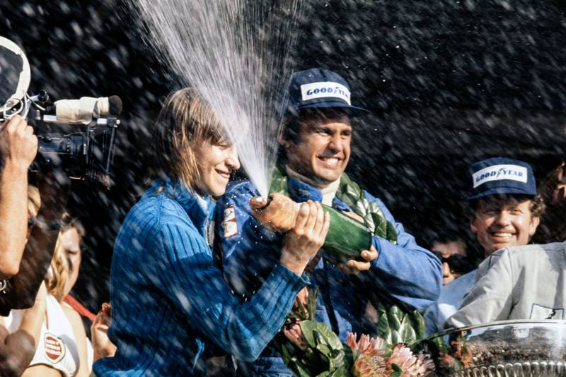 Carlos Reutemann celebrates on the podium afterw inning the 1974 South African Grand Prix.