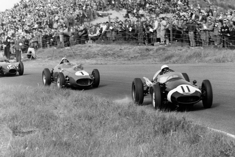Stirling Moss driving the Cooper T51-Climax leads Jean Behra in his Ferrari Dino 246 and Graham Hill in a Lotus 16-Climax.